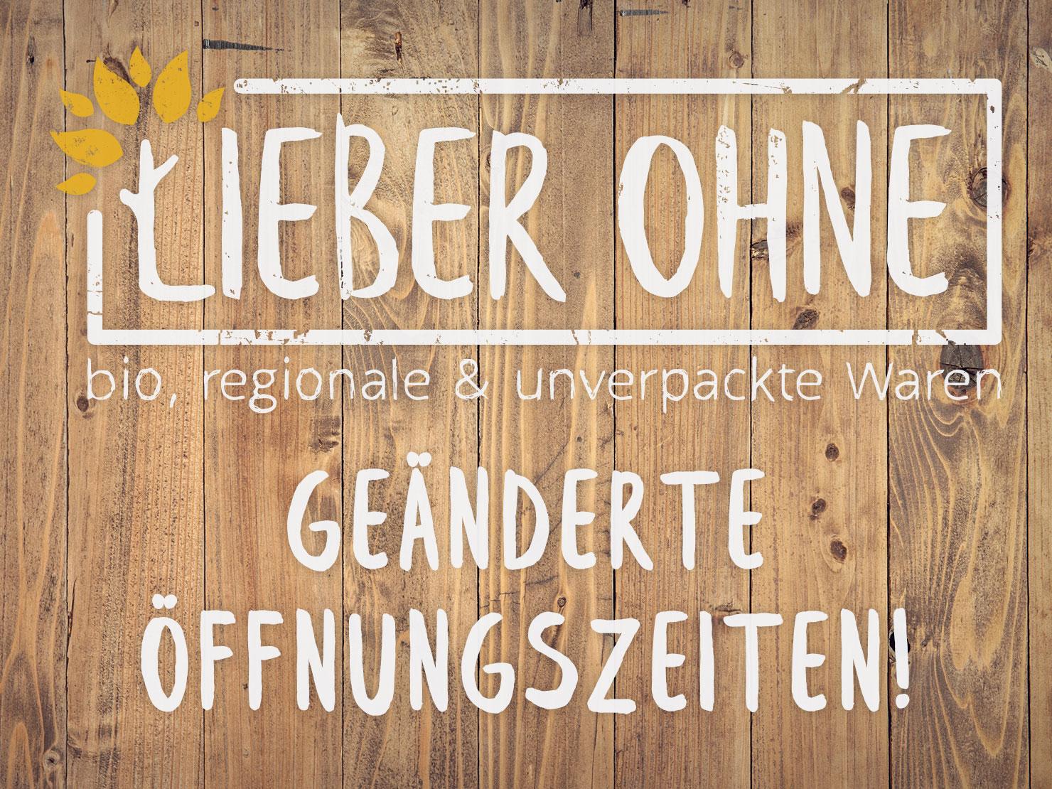 """Das Logo von Lieber Ohne und der Text """"Geänderte Öffnungszeiten"""" auf Holz"""