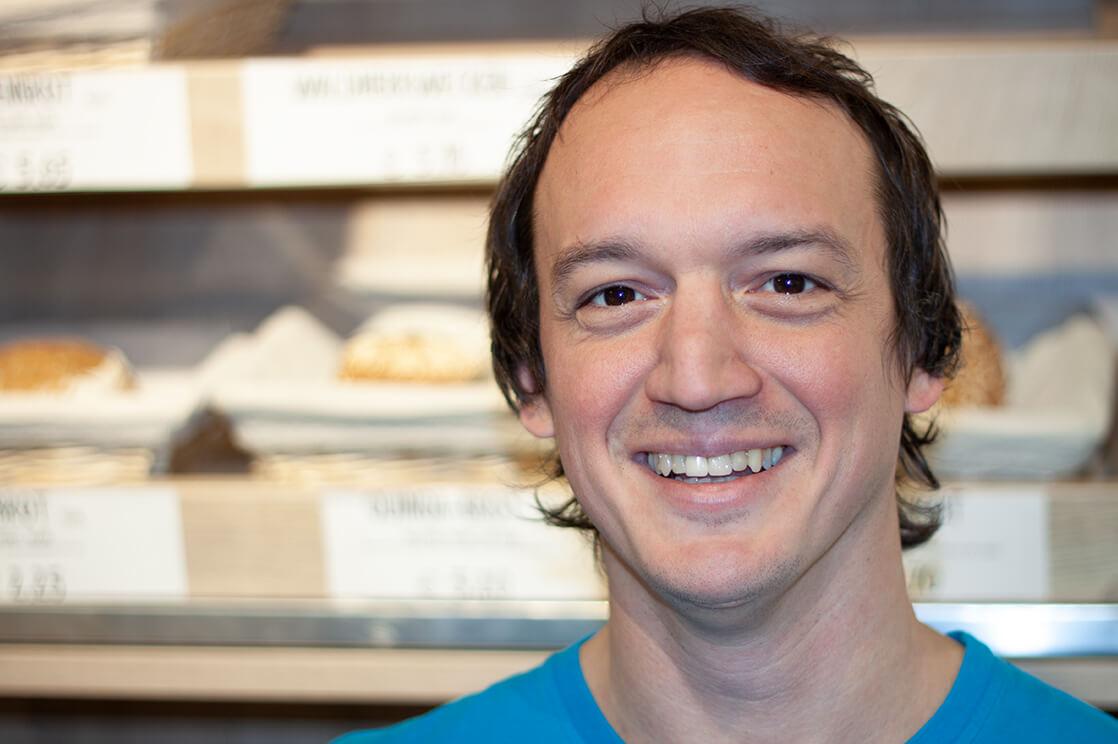 Ein Foto von Markus. Er hat kurze braune Haare, trägt ein blaues T-Shirt und lächelt